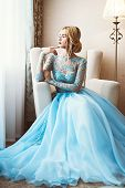 Full length portrait of a magnificent young woman in elegant long blue dress. Luxurious apartments.  poster