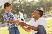African American Father Hands New Soccer Ball to Mixed Race Son at the Park.