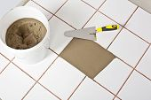 stock photo of mortar-joint  - broken white tile filled with tile adhesive with trowel and product package - JPG