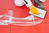 picture of grout  - Worker with rubber trowel applying white grout on red tile diagonally - JPG