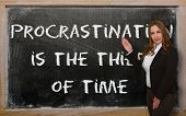 Teacher Showing Procrastination Is The Thief Of Time On Blackboard