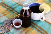stock photo of cough syrup  - Cough syrup on knitted scarf close - JPG