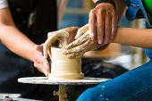 stock photo of pottery  - Female Potter creating a bowl on a Potters wheel - JPG