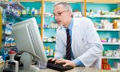 Portrait of a pharmacist using a desktop computer