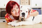 Happy woman with a young albino boxer dog in her office