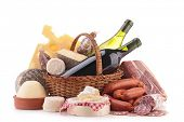 wicker basket with sausage, wine and cheese