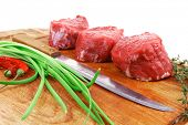 raw meat : fresh beef fillet with thyme and red hot dry pepper on wooden plate . isolated over white