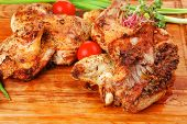 grilled meat : chicken quarters garnished with green sprouts and red peppers on wooden plate isolate