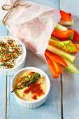 stock photo of dipping  - Delicious vegetables and spicy yogurt dip on a blue - JPG