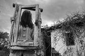 Horror Scene Of A Scary Girl Over A Spooky Abandoned House Background