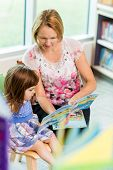stock photo of schoolgirls  - Mature teacher with schoolgirl reading book in library - JPG