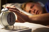 stock photo of turn-up  - Teenage Boy Waking Up In Bed And Turning Off Alarm Clock - JPG
