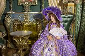 The little girl in old-fashioned dress with fan sitting in beautiful room with gilded furniture