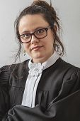 stock photo of toga  - thirtie something brunette woman wearing a canadian lawyer toga with her arm folded - JPG
