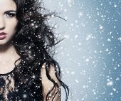 Portrait of young, beautiful and emotional brunette woman over blowing wind and snowy blizzard