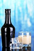 foto of bailey  - Baileys liqueur in bottle and glass on blue background - JPG