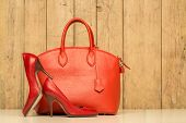 image of stiletto heels  - Woman accessories on wood background red handbag and high heels - JPG