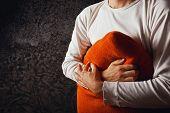 picture of grief  - Man hugging orange pillow in dark room - JPG