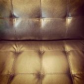 stock photo of futon  - Close-up of retro style leather sofa in warm golden light. ** Note: Soft Focus at 100%, best at smaller sizes - JPG