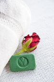 foto of panchakarma  - Stilllife with ayurvedic herbal soap with cachet Green Leaf red rose and towel - JPG