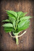 foto of sting  - Buch of stinging nettle on a wooden background - JPG