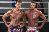 picture of muay thai  - Two Caucasian Muay Thai fighters pose without shirts in the ring as they flex their muscles - JPG