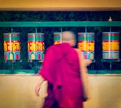 stock photo of himachal pradesh  - Vintage retro effect filtered hipster style travel image of Buddhist monk passing and rotating prayer wheels on kora around Tsuglagkhang complex in McLeod Ganj - JPG