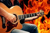 stock photo of serenade  - man playing guitar against fire background - JPG