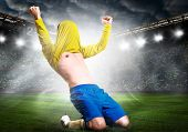pic of kneeling  - soccer or football player is celebrating goal on stadium with his jersey on head - JPG