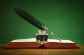 picture of inkpot  - Quill pen and inkwell resting on an old book with green background concept for literature - JPG