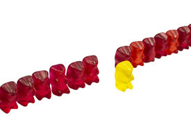 stock photo of gummy bear  - yellow Bear with other red Gummy Bears isolated on white - JPG