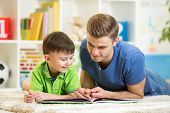 pic of nurture  - child boy and his dad read a book on floor at home - JPG