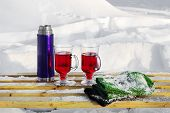 pic of thermos  - Thermos bottle two glasses of mulled wine and mittens on a snow - JPG