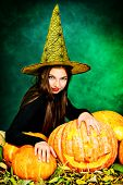 image of teen smoking  - Pretty teen girl in a costume of witch standing with pumpkins over dark smoky background - JPG