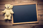 stock photo of teddy  - blank chalkboard and teddy bear on wooden table - JPG