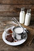 stock photo of bittersweet  - Metal mug and glass bottles of milk with chocolate chunks and strainer of cocoa on plate with burlap cloth and rustic wooden planks background - JPG