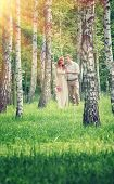 foto of birching  - Loving couple walking between birch in the park on sunny day - JPG