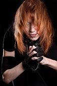 stock photo of flowing hair  - Portrait of a young woman with a flowing hair and chained arms over black background - JPG