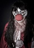 picture of horrific  - Unidentifiable woman in halloween clown costume with painted eyes - JPG