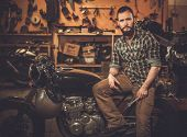 stock photo of rockabilly  - Rider and his vintage style cafe - JPG