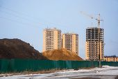 stock photo of early spring  - Heaps of chernozem and sand behind fence on building site of inhabited microdistrict of city in early spring - JPG
