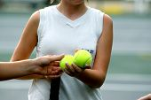 pic of tennis elbow  - tennis player shares tennis balls before a game - JPG
