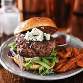 stock photo of gourmet food  - gourmet burger with blue cheese and sweet potato fries on metal plate - JPG