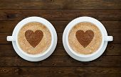 foto of two hearts  - Two cups of latte coffee with hearts on the wooden table - JPG