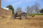 foto of punjabi  - punjabi agricultural landscape with a cattle egret beneath a tractor equipped to prepare for planting okra in a cultivated field - JPG