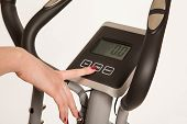 image of cardio  - female hand on cardio trainer computer button - JPG