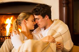 stock photo of cuddle  - affectionate young couple in love cuddling near fireplace - JPG