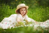 picture of girlie  - Little happy girl is sitting and resting on the grass - JPG