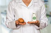 stock photo of human egg  - Young doctor holding two eggs and bottle of pills with vitamins and compare them - JPG