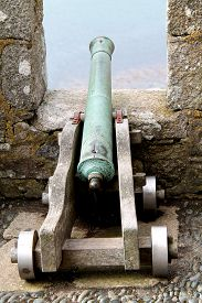 stock photo of cannon-ball  - A Vintage Cannon on a Castle Gun Emplacement - JPG